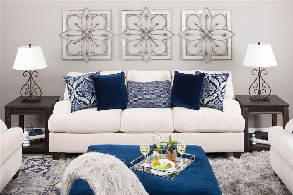 Cream sofa with blue accent pillows and a blue ottoman in the foreground